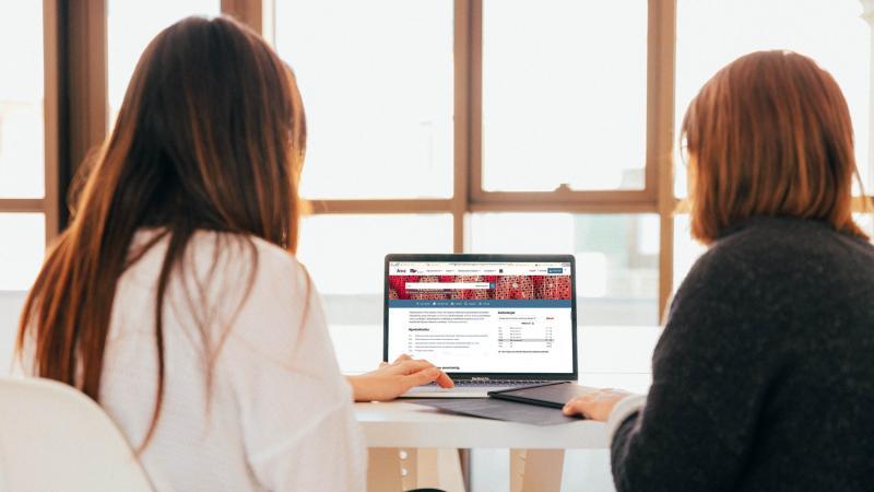 Kaksi ihmistä tietokoneella takaapäin kuvattuna.