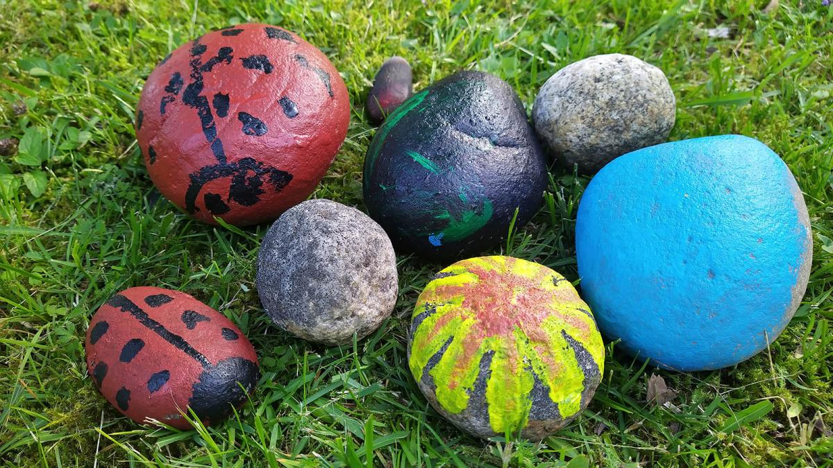 Painted garden rocks on grass