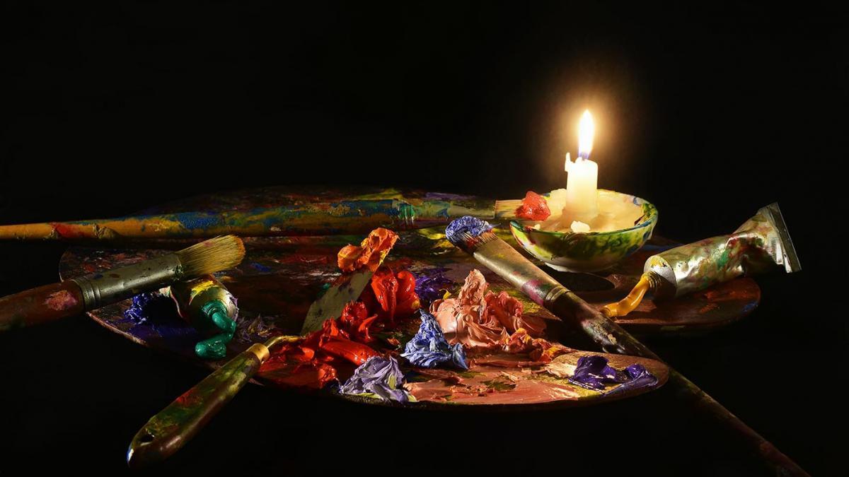 Maalaustarvikkeita ja kynttilä pöydällä.