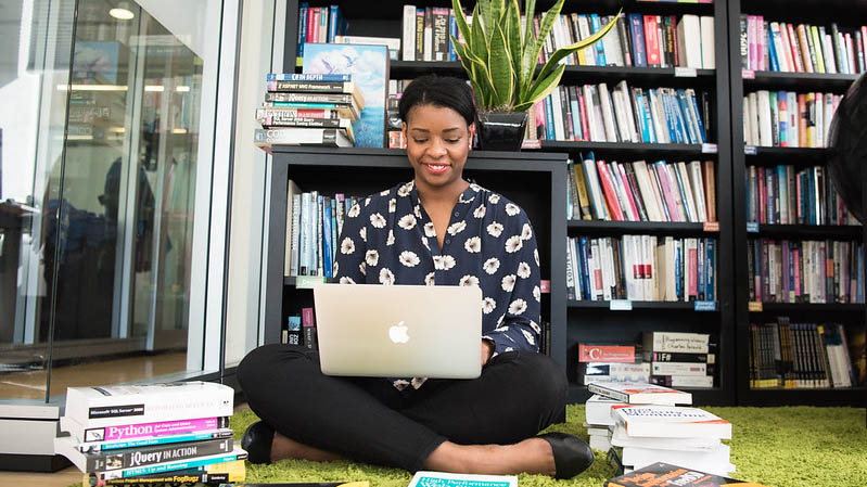 Nainen istuu lattialla, kannettava tietokone sylissään. Lattialla ja taustalla olevassa hyllyssä on kirjoja.