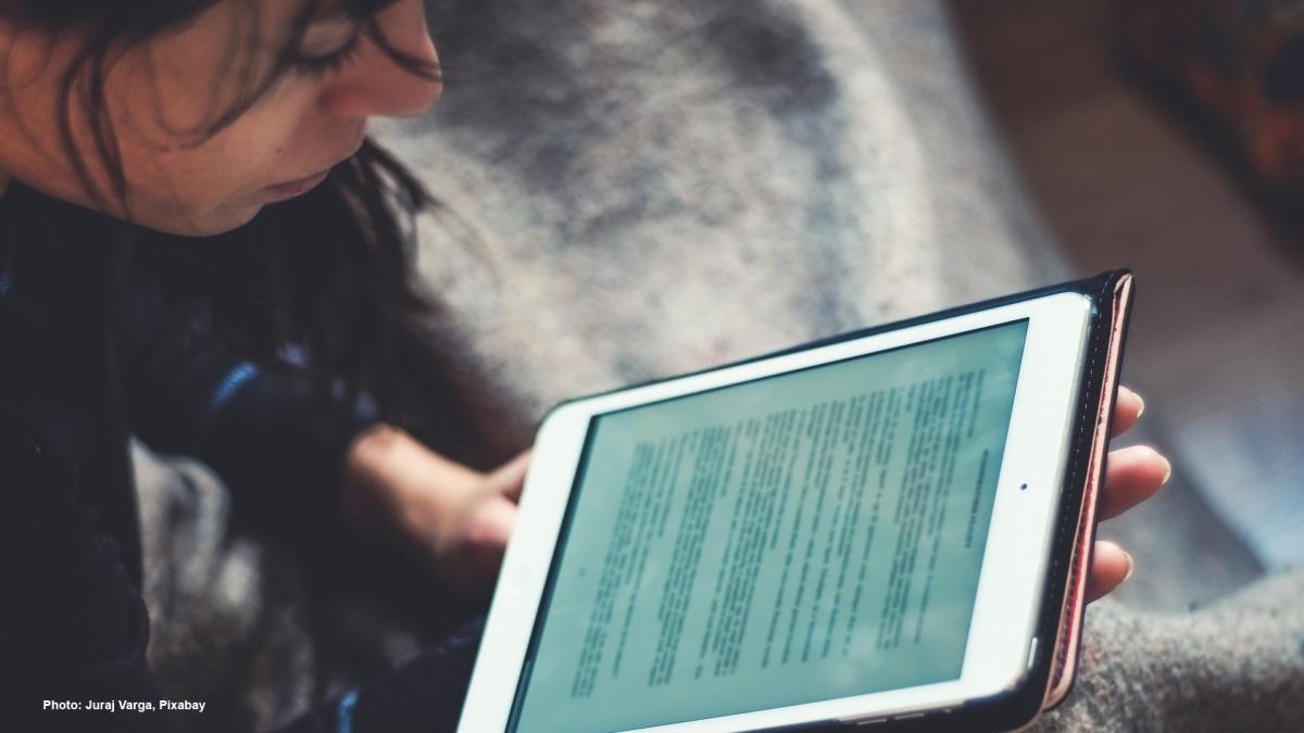 Henkilö lukee e-kirjaa.