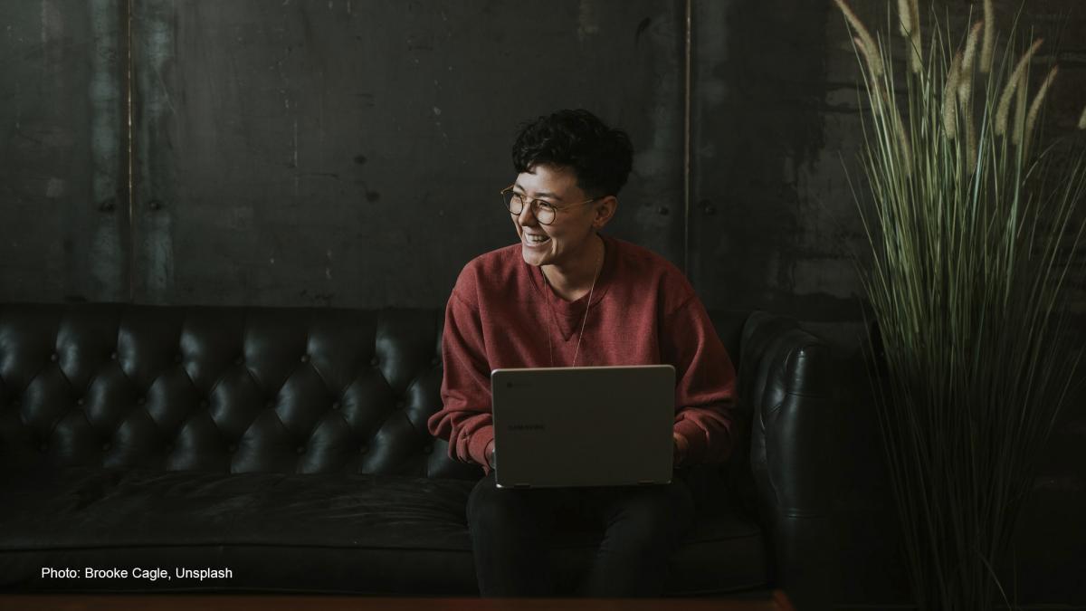Hymyilevä henkilö istuu sohvalla kannettava tietokone sylissään.