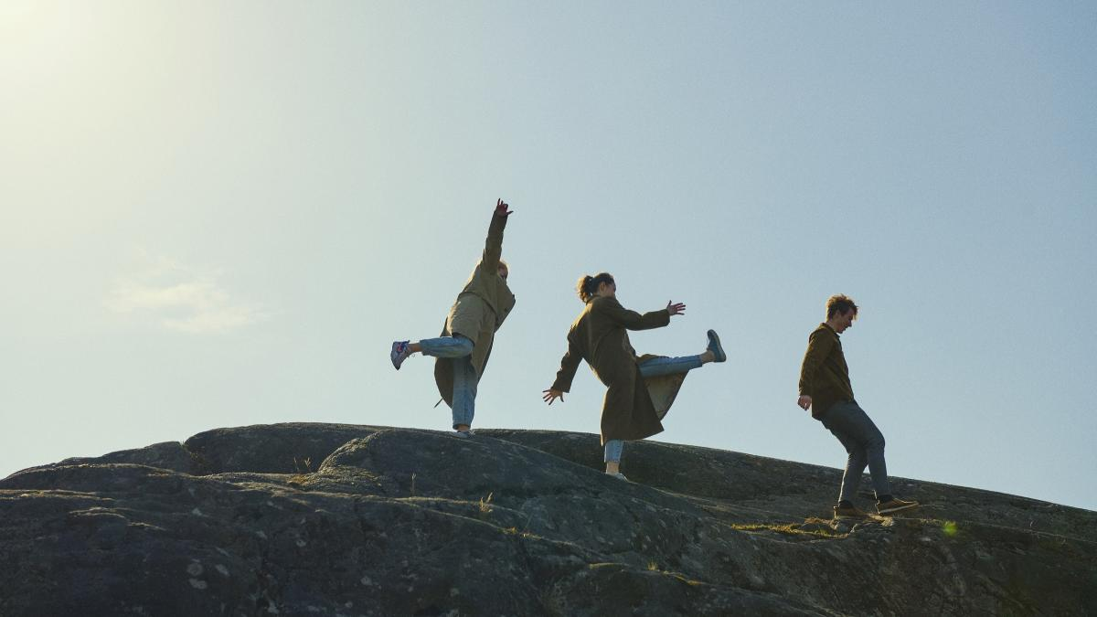 Three people on a rock pictured against the sky.