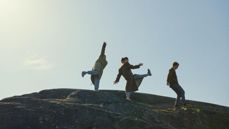 Kolme henkilöä kalliolla taivasta vasten kuvattuna.