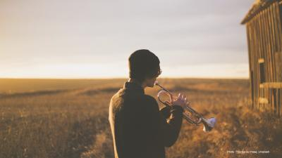 A person plays a trumpet in a field.