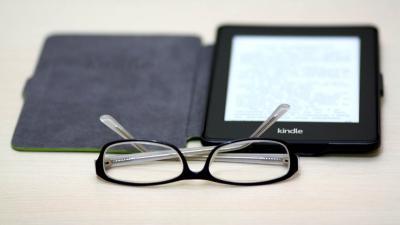 Silmälasit ja Kindle-lukulaite pöydällä.