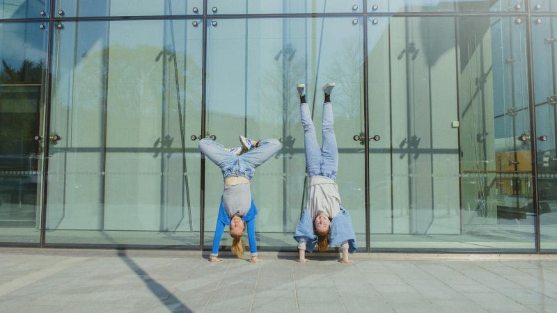 Two persons standing on their hands in front of a building.