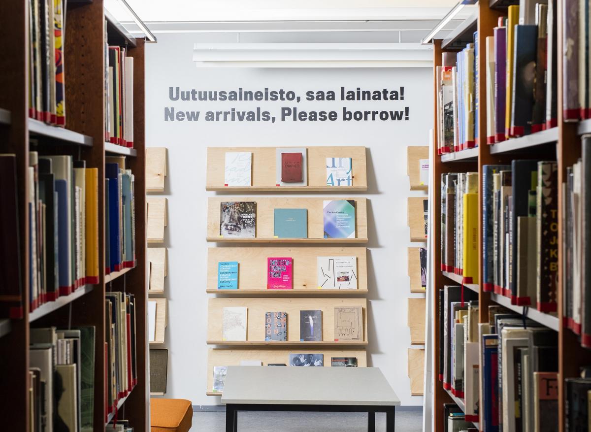 """Kirjahyllyjä, seinällä teksti """"Uutuusaineistoa, saa lainata!""""."""