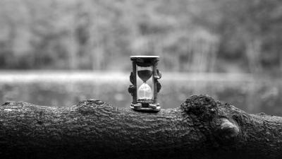 A black and white photograph of an hourglass standing on a tree log.